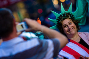 Tourist taking picture of his wife dressed as Statue of Liberty