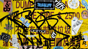 Yellow sign with graffiti and stickers