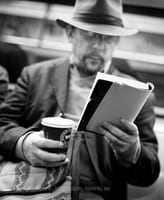 Man is reading book and drinking coffee on the subway