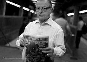 Man reading his news paper in subway