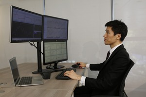 A trader at a desk with three monitors and a laptop