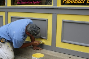 Painter is painting outside a store