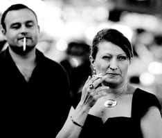 Guy that smokes is looking at a lady that also smokes
