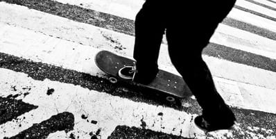 Person with skateboard on pedestrian crossing