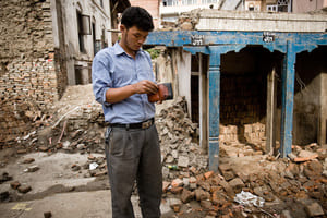 Guy inspecting his wallet among ruins